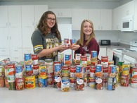 Two students standing behind dozens of cans of collected soup